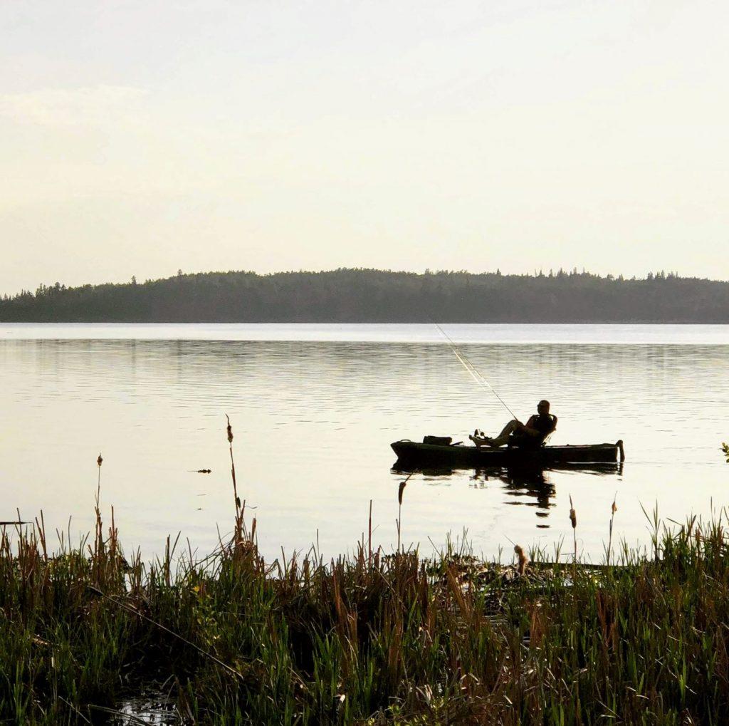 Kayak fishing on calm lake